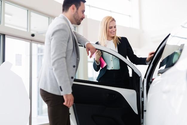 Профессиональный продавец, продающий автомобили в автосалоне новому покупателю