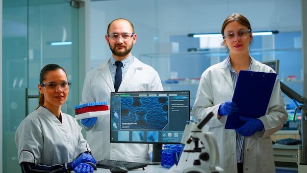 近代的な設備の整ったラボでカメラを見ているプロの科学医療スタッフ。ハイテク、科学研究のための化学ツール、ワクチン開発でウイルスの進化を調べる医師のチーム