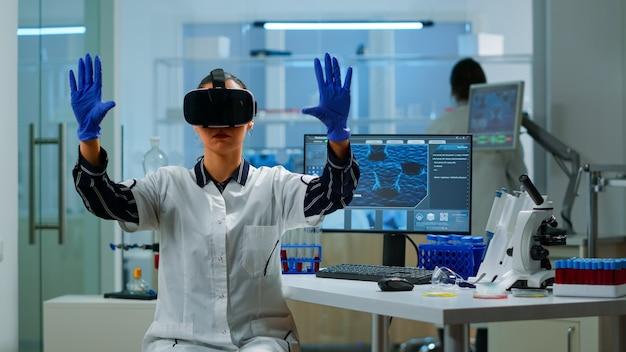 研究室で医療イノベーションを使用してバーチャルリアリティメガネを着用しているプロの科学者。機器デバイス、未来、医学、ヘルスケア、専門家、ビジョン、シミュレーターを扱う研究者のチーム