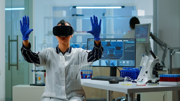Professional scientist wearing virtual reality glasses using medical inovation in lab. team of researchers working with equipment device, future, medicine, healthcare, professional, vision, simulator