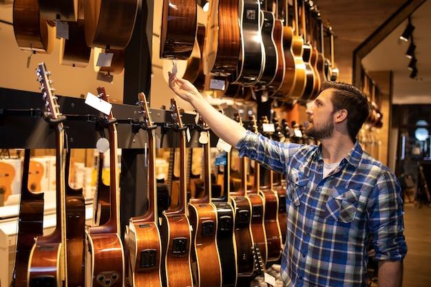 Профессиональный продавец стоит в музыкальном магазине и проверяет цены на продажу гитар.