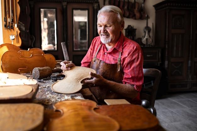 Профессиональный старший плотник, изготавливающий высококачественный скрипичный инструмент для студентов музыкальной академии.