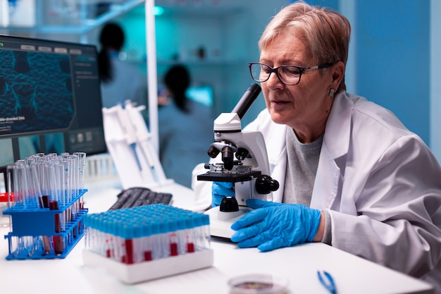Professional senior scientist using microscope in health study