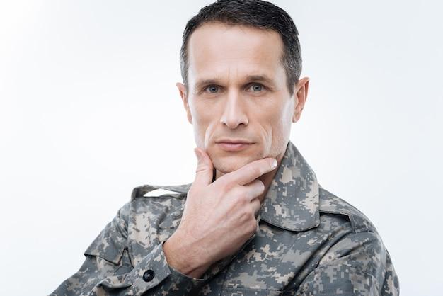 Профессиональный военнослужащий. вдумчивый хороший военный мужчина держится за подбородок и думает о проблеме, ища решение