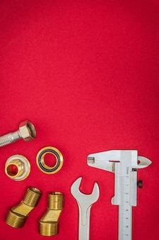 Professional set of tools and spare parts for plumbing on red desktop with space for advertising