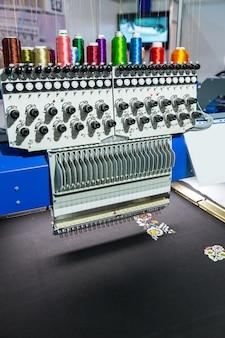 Вышивка цветного узора на текстиле на профессиональной швейной машине, никто. заводское производство, швейное производство, технология рукоделия