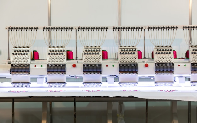Professional sewing machine in work on textile fabric, nobody. factory production, sew manufacturing, needlework technology