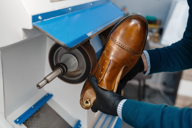 Professional shoemaker processes the sole of the shoe, footwear repair.