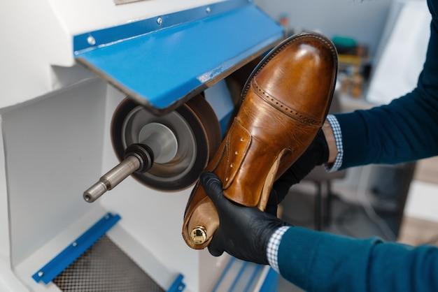 Профессиональный сапожник обрабатывает подошву обуви, ремонт обуви.