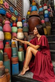 전문 촬영. 다채로운 도자기를 보면서 계단에 반 위치에 앉아 예쁜 여자