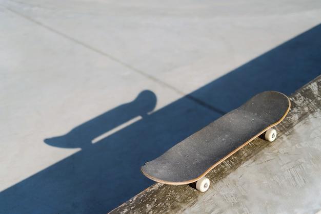 Укладка профессионального скейтборда на бетонную полку в скейт-парке.