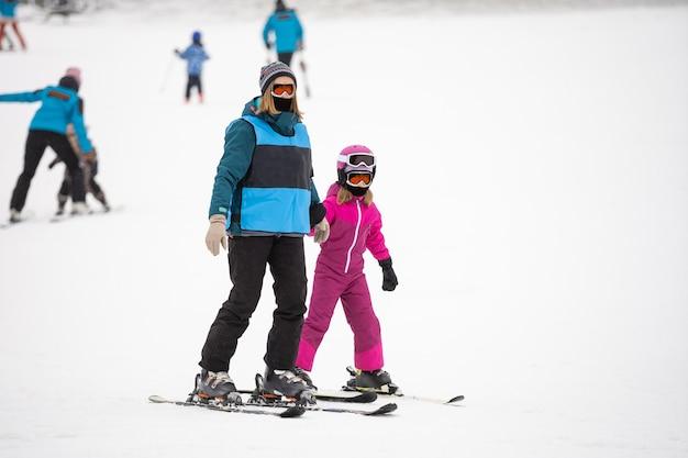 Профессиональный лыжный инструктор обучает ребенка кататься на лыжах в день на горнолыжном курорте со снегом. семейный и детский активный отдых.