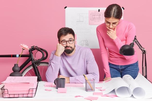 공동 작업 공간에서 포즈를 취하는 전문 숙련 된 여성 및 남성 건축가는 공동 프로젝트를 만들기 위해 공동 작업하여 현대 사무실의 스케치 학습 과정에서 창의적인 아이디어를 논의합니다. 팀워크 개념