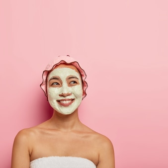Professional skin care concept. happy ethnic woman applies facial mask for cleansing and moisturizing skin, looks with dreamy happy expression, toothy smile, wrapped in soft towel, poses indoor