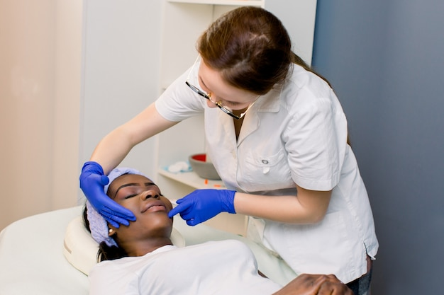 Professional skincare. beautiful nice african woman visiting a cosmetologist while caring about her skin
