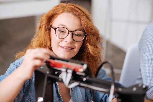 Профессиональный умный позитивный дизайнер смотрит на печатную машину и настраивает ее, тестируя 3d-технологию