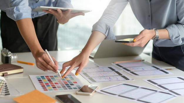 A professional smartphone application design team is designing a new project in a modern office.