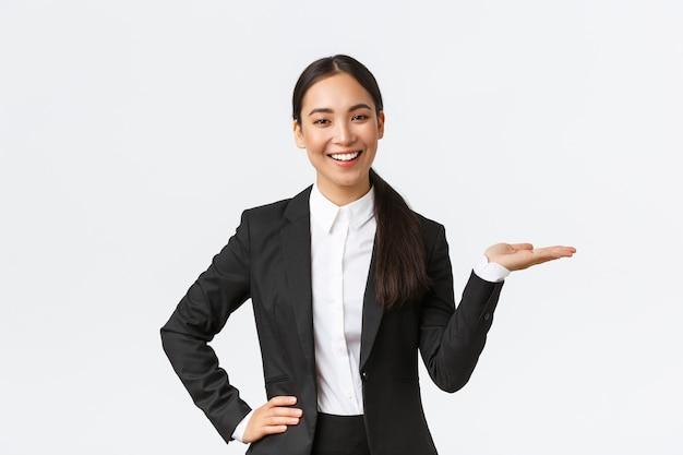 Профессиональный улыбающийся предприниматель представляет свой проект во время встречи. продавщица в черном костюме, держащая руку вправо, показывая продукт, держа ладонь на пустом белом фоне