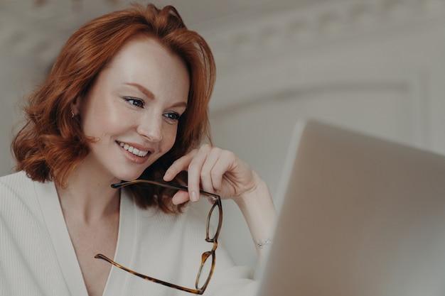 Профессиональная улыбающаяся рыжая веб-дизайнер использует приложение на портативном компьютере для создания проектной работы, проводит онлайн-исследования и просматривает интернет, проводит очки, имеет счастливое выражение