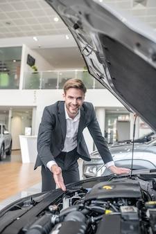 Профессиональный. улыбающийся молодой взрослый приветливый мужчина в белой рубашке и темном костюме показывает рукой в открытом капоте автомобиля в автосалоне