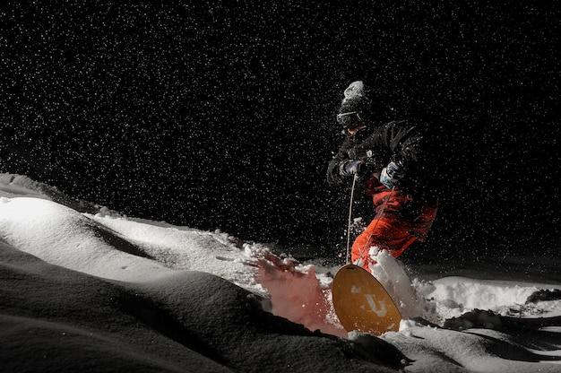 Профессиональный сноубордист едет по снежной горке ночью
