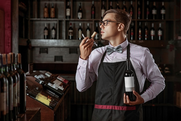 Professional sommelier smelling a cork from a freshly opened wine bottle