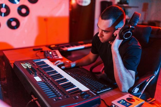 전문 사운드 엔지니어는 스튜디오에서 실내에서 음악을 작업하고 믹싱합니다.