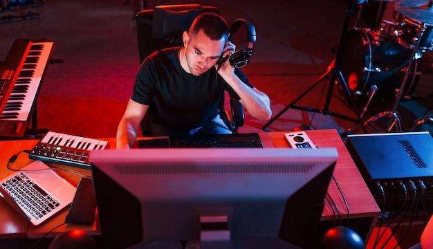 スタジオの屋内で音楽を演奏およびミキシングするプロのサウンドエンジニア。