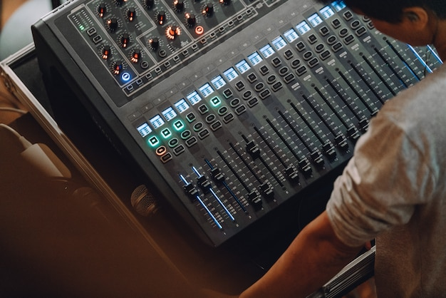 Professional soundboard including audio mixer control panel with buttons and sliders.