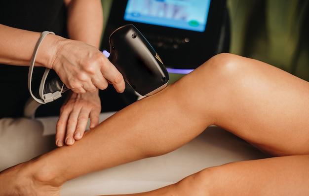 Профессиональный спа-работник делает сеанс эпиляции на ногах с дамой