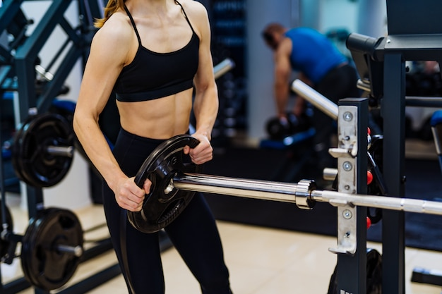 Professional sport fitness woman putting weight disk to barbell in gym.