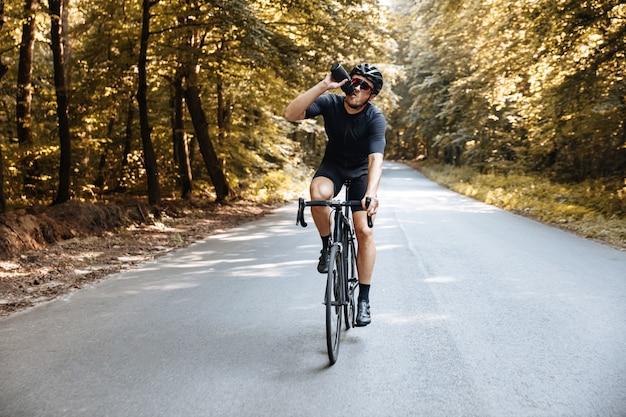 Профессиональный спортсмен в активной одежде и защитном шлеме пьет воду во время езды на велосипеде на свежем воздухе.