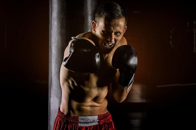 Профессиональный спортсмен смешанных единоборств стоит в боевой стойке и бьет кримом по врагу.