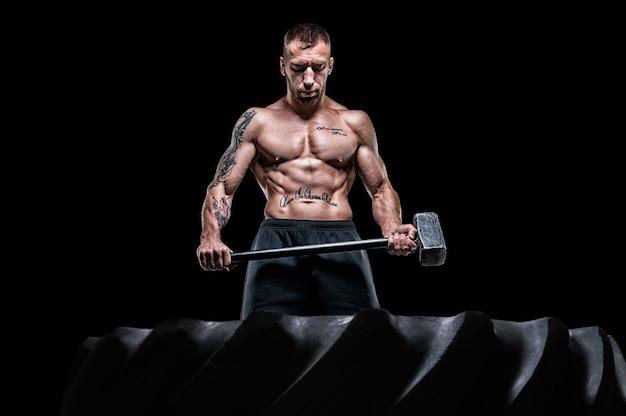 プロスポーツマンは、ゴム製の車輪の前にハンマーで立っています。ファンクショナルトレーニングのコンセプト。ミクストメディア