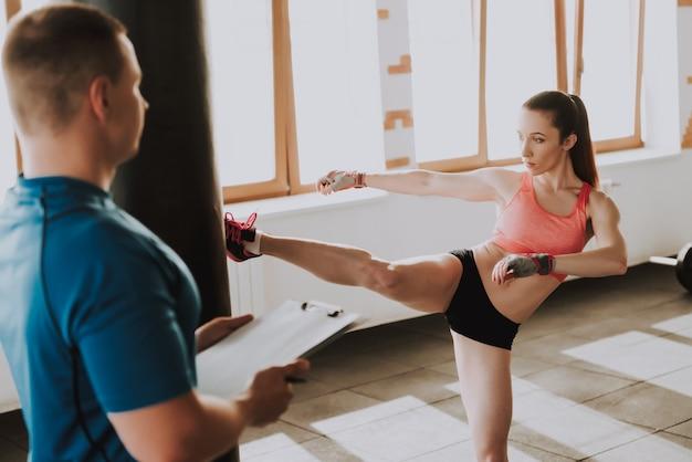 Professional sportswoman is kicking punching bag.