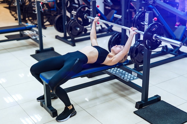 Professional sporty woman builds muscle arms and chest on the simulator in the gym.