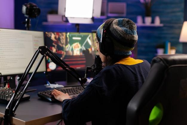 전문 스트리머가 헤드폰을 끼고 슈팅 게임을 하고 스트리밍 채팅을 통해 마이크에 대고 이야기합니다. 강력한 컴퓨터에서 새로운 그래픽으로 온라인 비디오 게임을 만드는 게이머