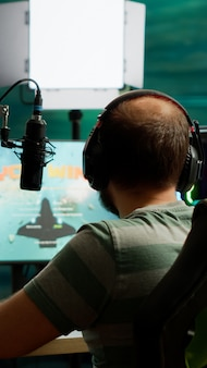 Videogioco sparatutto spaziale vincitore di streamer professionista in una competizione dal vivo che gioca da casa studio