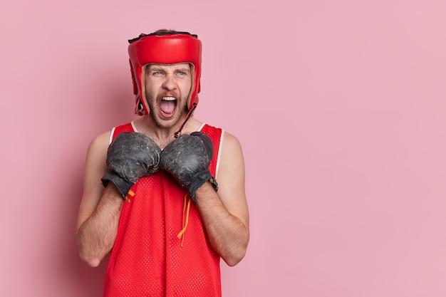 전문 강한 남성 권투 선수는 권투 장갑을 끼고 링에서 싸울 준비가 된 수비 포즈에서 큰 소리로 외칩니다.