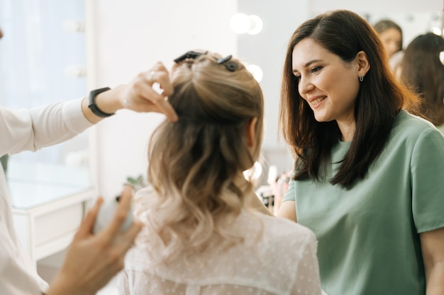 若い女性のためのメイクアップとスタイルの髪をやっているプロのスタイリストとメイクアップアーティスト