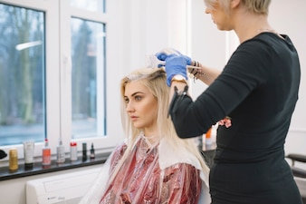 Professional stylist coloring hair of client