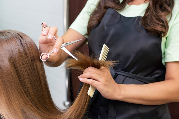 Профессиональный стилист стрижет женские волосы в салоне
