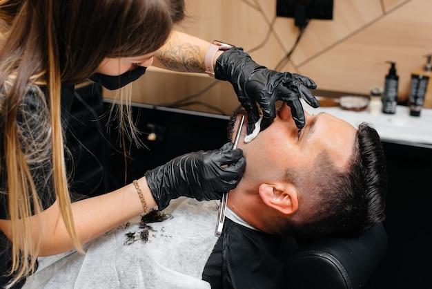 モダンでスタイリッシュな理髪店のプロのスタイリストが若い男の髪を剃ってカットします