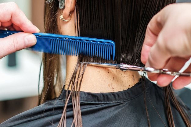 전문 스타일리스트가 검은 머리카락을 자르고 있습니다.