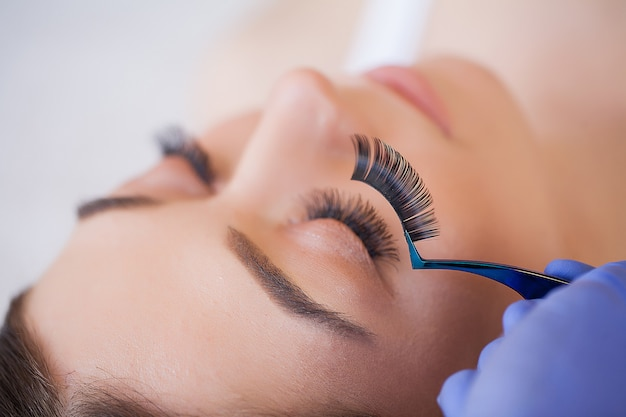 Professional stylist lengthening female lashes.