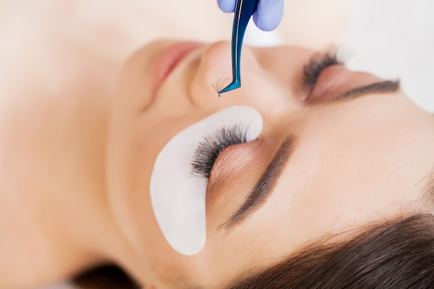 Professional stylist lengthening female lashes
