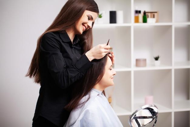 전문 스타일리스트는 젊은 여성을 아름다운 헤어 스타일로 만듭니다.