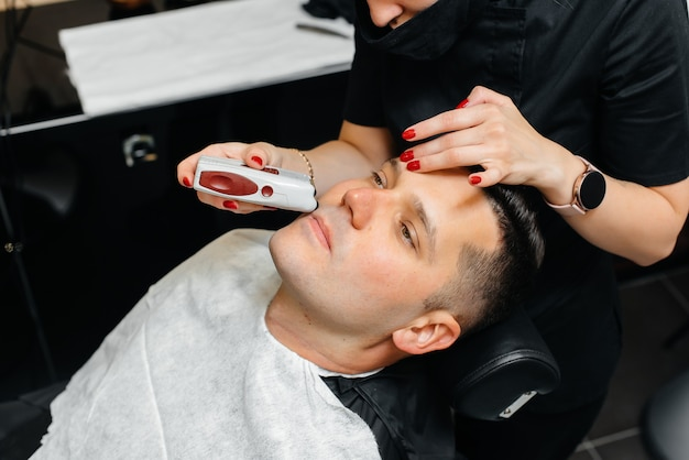 Professional stylist in a modern stylish barbershop shaves and cuts a young man's hair