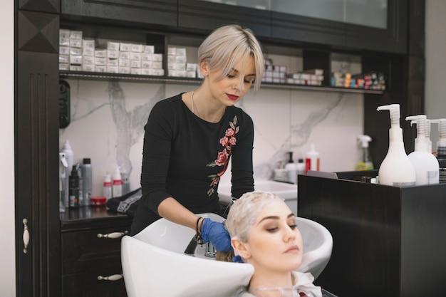 Stilista professionista che lava i capelli del cliente