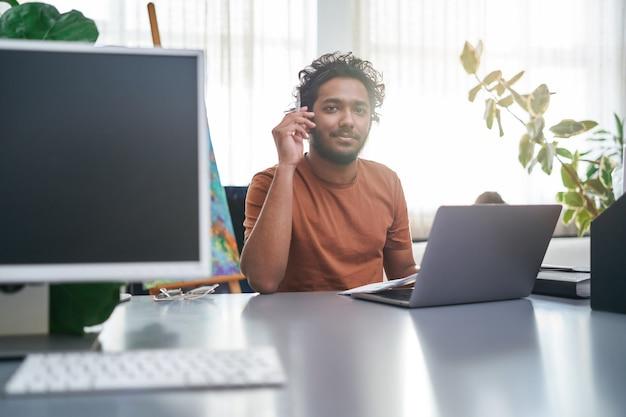 ノートパソコンを持ったプロのスタイリストが、昼間の窓の背景でポーズをとります。インドのデザイナーがカメラを見ています。